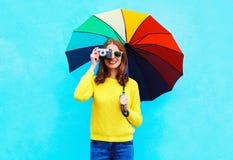 Glückliche lächelnde junge Frau mit der Weinlesekamera, die bunten Regenschirm am Herbsttag über blauem Hintergrund hält Stockbilder