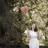 Glückliche lächelnde junge Frau mit einem roten geformten Herz-Ballon Stockbild