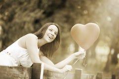 Glückliche lächelnde junge Frau mit einem roten geformten Herz-Ballon Stockfotos