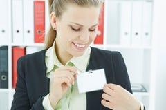 Glückliche lächelnde junge Geschäftsfrau, die leeren Ausweis trägt Stockfotografie