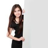 Glückliche lächelnde junge Geschäftsfrau, die leeres Schild zeigt Lizenzfreie Stockfotos