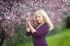 Glückliche lächelnde kaukasische blonde Frau mit dem langen Haar im nahen blühenden Pflaumenkirschbaum des purpurroten Fedorahute Lizenzfreies Stockbild