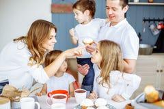Glückliche lächelnde kaukasische Familie, die in der Küche frühstückt stockbilder