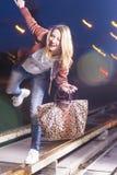 Glückliche lächelnde kaukasische Frau in der Lederjacke und in Blue Jeans, die draußen auf Schienen mit Tasche nachts spielen Lizenzfreies Stockbild