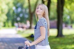 Glückliche lächelnde kaukasische Jugendliche, die draußen mit langem Skateboard aufwirft Stockfotos
