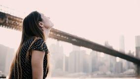 Glückliche lächelnde kaukasische junge Frau, die auf dem Flussdammzaun, New- Yorkbrooklyn-brücken-Panorama 4K genießend sitzt stock video footage