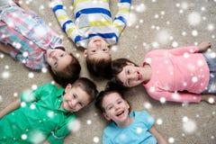 Glückliche lächelnde Kinder, die auf Boden über Schnee liegen Stockfotos