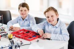 Glückliche lächelnde Kinder, die nahe Tabelle sitzen Stockbilder