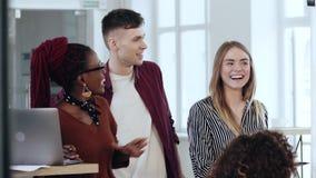Glückliche lächelnde multiethnische Geschäftsleute arbeiten, Diskussion während der modernen Bürokonferenz am gesunden Arbeitspla stock footage