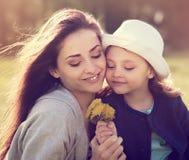 Glückliche lächelnde Mutter, die ihre Tochter im Hut umfasst Stockfotografie
