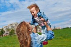 Glückliche lächelnde Mutter, die junge Kleinkindtochter hält stockfoto