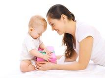Glückliche lächelnde Mutter und Baby mit Geschenkbox auf einem Weiß Lizenzfreie Stockfotos