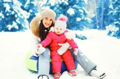 Glückliche lächelnde Mutter und Kind des Winters, die auf Schlitten am schneebedeckten Tag sitzt Stockfotos