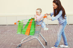 Glückliche lächelnde Mutter und Kind mit Laufkatzenwarenkorb und -Einkaufstaschen Stockfoto