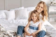 Glückliche lächelnde Mutter und Tochter, die auf Bett umarmt Lizenzfreie Stockbilder