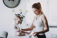 Glückliche lächelnde Mutter zieht entzückendes Kind zu Hause ein stockfotografie