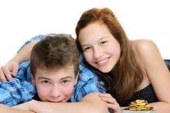 Glückliche lächelnde Paare in der Liebe, die auf dem Boden, getrennt auf weißem Hintergrund liegt Lizenzfreie Stockfotografie