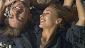 Glückliche lächelnde Paare in der Liebe, die auf dem Strand liegt stock video footage