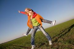 Glückliche lächelnde Paare, die in Himmel springen Lizenzfreie Stockfotografie