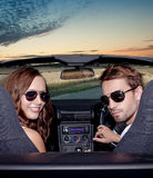 Glückliche lächelnde Paare in einem konvertierbaren Auto. Leute draußen. Stockbilder