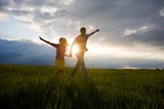 Glückliche lächelnde Paare laufen gelassen auf das Feld Stockfotografie