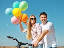 Glückliche lächelnde Paare mit Ballonen Lizenzfreie Stockfotos