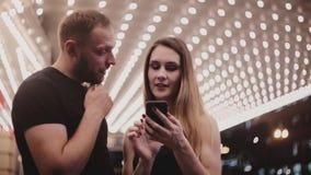 Glückliche lächelnde Paare von den touristischen Freunden, die wenn Chicago-Theater unter Verwendung der Smartphonekarte stehen,  stock video footage