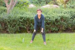 Glückliche lächelnde schöne ältere Frau, die Sportübungen mit Dummköpfen in einem Park an einem sonnigen Tag tut stockbild