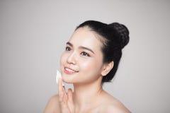 Glückliche lächelnde schöne asiatische Frau, welche die Baumwollauflage säubert SK verwendet Stockbild