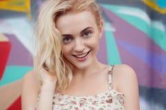 Glückliche lächelnde schöne blonde Frau des Porträts mit blauen Augen Stockfotos