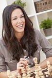 Glückliche lächelnde schöne Frau, die Schach spielt Lizenzfreies Stockfoto