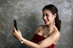 Glückliche lächelnde schöne junge sexy Frau im roten Partykleid verscheuchen Stockfotos