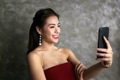 Glückliche lächelnde schöne junge sexy Frau im roten Partykleid verscheuchen Lizenzfreies Stockfoto