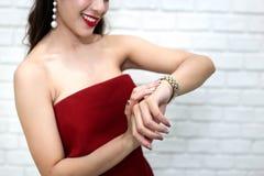 Glückliche lächelnde schöne junge sexy Frau im roten Partykleidblick Stockbild
