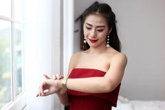 Glückliche lächelnde schöne junge sexy Frau im roten Partykleidblick Lizenzfreie Stockbilder