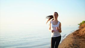 Glückliche lächelnde Sportfrau, die auf dem Sandstrand nahe dem Meer rüttelt stock video footage
