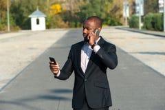Glückliche lächelnde städtische Professioneller, die intelligentes phone01 verwendet Stockfotos