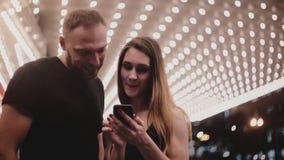 Glückliche lächelnde touristische Jungvermähltenpaare schauen herum, wenn sie Chicago-Theater unter Verwendung des Smartphone übe stock footage