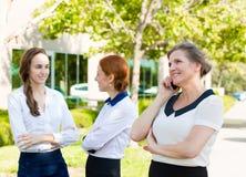 Glückliche, lächelnde Unternehmensarbeitskraft, die am Handy spricht Stockbild