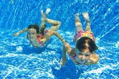 Glückliche lächelnde Unterwasserkinder im Swimmingpool Stockfotografie