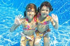 Glückliche lächelnde Unterwasserkinder im Swimmingpool stockfoto