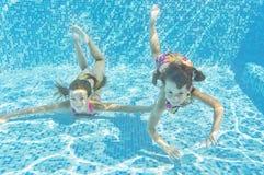 Glückliche lächelnde Unterwasserkinder im Swimmingpool Lizenzfreie Stockbilder