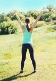 Glückliche Läuferfrau der Eignung, die nach im Park, im Läufersieger, in den Erhöhungshänden, im Sport und im gesunden Lebensstil Lizenzfreies Stockfoto