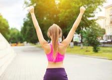 Glückliche Läuferfrau der Eignung, die nach im Stadtpark, im Läufersieger, in den Erhöhungshänden, im Sport und im gesunden Leben Lizenzfreies Stockbild