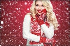 Glückliche lachende blonde Frau kleidete in der Weihnachtsabnutzung denken an Sankt an, lokalisiert auf rotem Hintergrund Stockbild