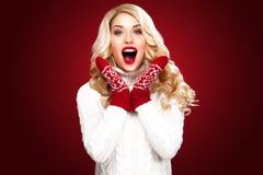 Glückliche lachende blonde Frau kleidete in der Weihnachtsabnutzung denken an Sankt an, lokalisiert auf rotem Hintergrund Stockfoto
