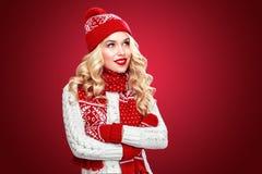 Glückliche lachende blonde Frau kleidete in der Weihnachtsabnutzung an, die auf Kopienraum, roter Hintergrund schaut Lizenzfreies Stockfoto