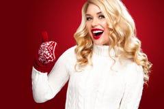 Glückliche lachende blonde Frau kleidete in der Weihnachtsabnutzung mit den Daumen oben, auf rotem Hintergrund an Lizenzfreie Stockfotografie