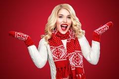 Glückliche lachende blonde Frau kleidete in der Weihnachtsabnutzung mit den Daumen oben, auf rotem Hintergrund haben Kopienraum a Lizenzfreie Stockfotos