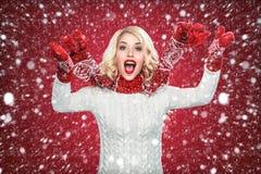Glückliche lachende blonde Frau kleidete in der Weihnachtsabnutzung mit den Daumen oben, auf rotem Hintergrund haben Kopienraum a Lizenzfreie Stockbilder